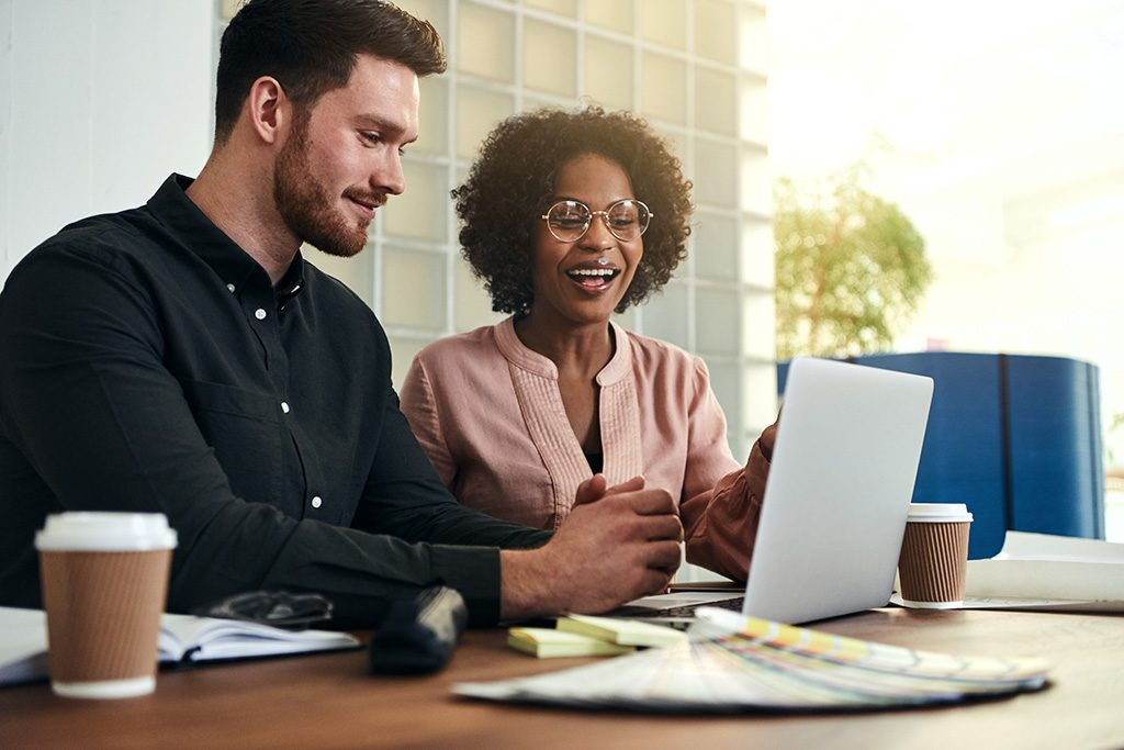man and woman look at laptop on desk discussing business process management