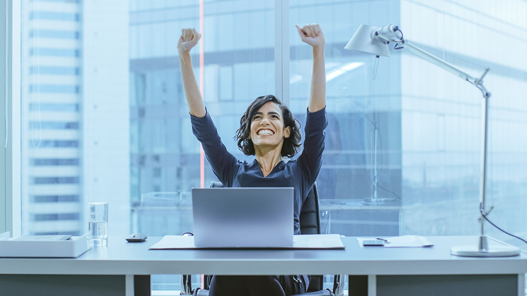 woman in office raises arms in victory of successful business process management