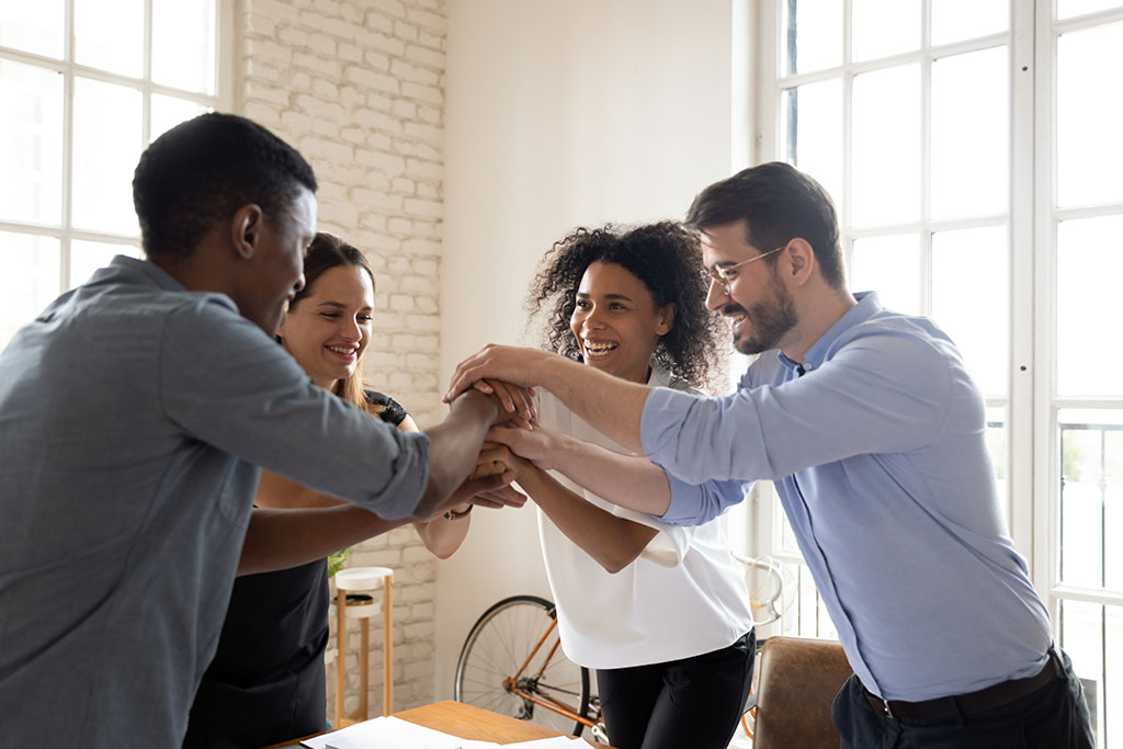 team of business people in a circle with hands in the center in a cheer represent workflow management