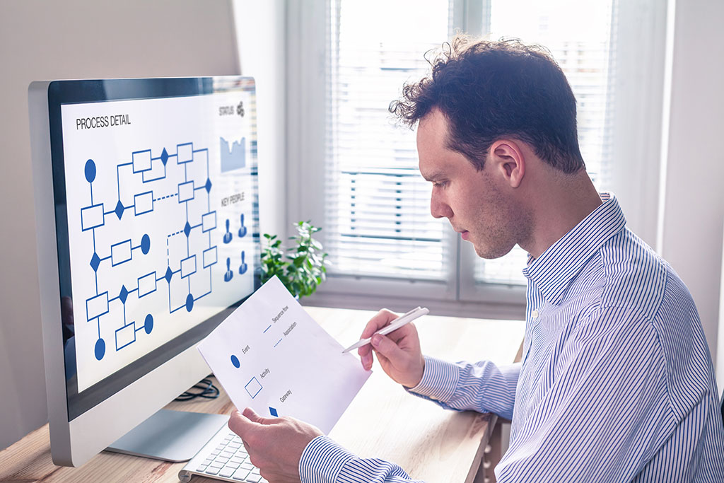 man looks at a business workflow on computer and paper